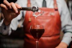 有增加冰块入玻璃和准备鸡尾酒的钳子的侍酒者 图库摄影