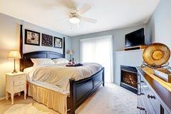 有壁炉和电视的主卧室 图库摄影