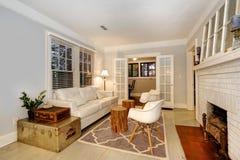 有壁炉的客厅、古色古香的胸口和现代沙发和c 库存图片