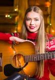 有声学吉他的女孩在欢乐环境里 免版税库存图片
