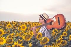 有声学吉他的时髦人士在向日葵领域 库存图片
