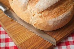 有壳的在顶端大面包视图在与刀子的木桌上 库存照片
