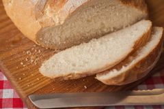有壳的在顶端大面包视图在木桌上并且由刀子slised 库存图片