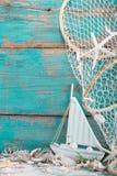 有壳的风船和在绿松石背景的捕鱼网为 免版税图库摄影