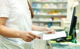有处方的药剂师在药房的医学前面 免版税库存图片
