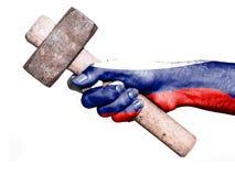 有处理一把重的锤子的俄罗斯的旗子的手 免版税库存图片
