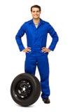 有备用轮胎的确信的男性技工 免版税图库摄影