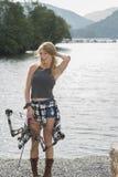 有复合弓的美丽的年轻白肤金发的女性射手 免版税库存照片