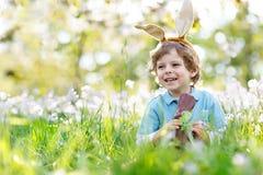 有复活节兔子耳朵的逗人喜爱的小孩男孩庆祝传统宴餐愉快的儿童吃巧克力兔子fugure的 库存照片