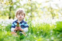 有复活节兔子耳朵的逗人喜爱的小孩男孩庆祝传统宴餐愉快的儿童吃巧克力兔子fugure的 免版税库存照片