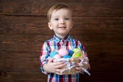 有复活节彩蛋篮子的愉快的男婴在木背景的 库存图片