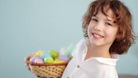 有复活节篮子的微笑逗人喜爱的小男孩看照相机 影视素材