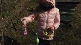有复活节装饰的女孩在室外的灌木附近 影视素材