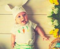 有复活节兔子耳朵和花的愉快的婴孩 免版税库存图片
