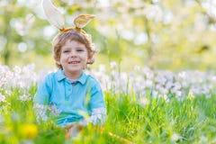 有复活节兔子耳朵的小孩男孩在春天 免版税库存图片