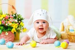 有复活节兔子耳朵的愉快的小孩子和鸡蛋和花 免版税图库摄影