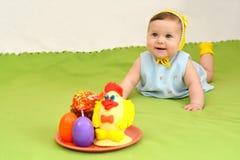 有复活节娱乐的快乐的婴孩在绿色背景 免版税库存图片