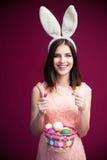 有复活节彩蛋篮子的微笑的美丽的妇女 免版税库存照片