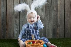 有复活节篮子的即Smilling小孩男孩佩带的兔宝宝耳朵  库存图片