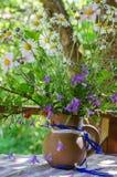 有夏天花束的水罐在一张桌上开花在庭院里 免版税库存照片