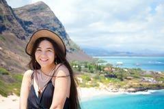 有夏威夷山和海滩后面的微笑的两种人种的青少年的女孩 免版税库存照片