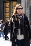 有外套、袋子、围巾和太阳镜的时髦的女人 免版税库存图片