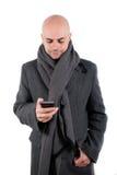 有外套和围巾的人使用他巧妙的电话。 免版税库存图片
