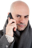 有外套和围巾的人在电话。 图库摄影