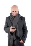 有外套和围巾的愉快的人使用他巧妙的电话。 免版税图库摄影