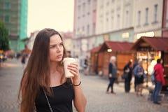 有外带的饮料步行的妇女在街道上 妇女举行一次性咖啡杯 咖啡或茶心情 饮料和食物在期间 库存照片
