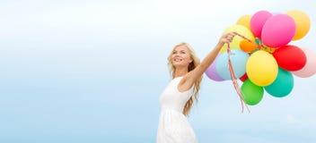 有外面五颜六色的气球的微笑的妇女 库存照片