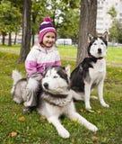 有外面多壳的狗的小逗人喜爱的女孩 免版税库存照片