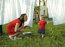 有外面孩子的妇女庭院垂悬的洗衣店的,使用与逗人喜爱的女婴小孩,生活方式人概念 免版税图库摄影