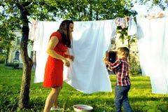 有外面孩子的妇女庭院垂悬的洗衣店的,使用与逗人喜爱的女婴小孩,生活方式人概念 库存照片