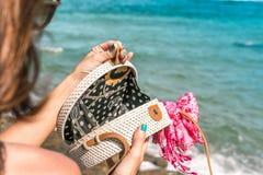 有外面时兴的时髦的白色藤条袋子和丝绸围巾的妇女手 巴厘岛,印度尼西亚热带海岛  藤条 库存照片