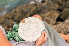 有外面时兴的时髦的白色藤条袋子和丝绸围巾的妇女手 巴厘岛,印度尼西亚热带海岛  藤条 库存图片