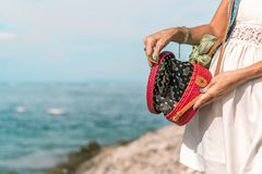 有外面时兴的时髦的红色藤条袋子和丝绸围巾的妇女手 巴厘岛,印度尼西亚热带海岛  藤条 免版税库存图片