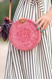 有外面时兴的时髦的红色藤条袋子和丝绸围巾的妇女 巴厘岛,印度尼西亚热带海岛  藤条提包 库存照片