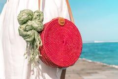 有外面时兴的时髦的红色藤条袋子和丝绸围巾的妇女 巴厘岛,印度尼西亚热带海岛  藤条提包 免版税库存图片
