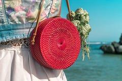 有外面时兴的时髦的红色藤条袋子和丝绸围巾的妇女 巴厘岛,印度尼西亚热带海岛  藤条提包 免版税图库摄影