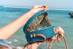 有外面时兴的时髦的蓝色藤条袋子和丝绸围巾的妇女手 巴厘岛,印度尼西亚热带海岛  藤条 库存照片