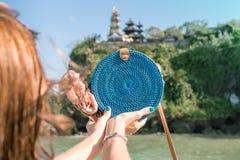 有外面时兴的时髦的蓝色藤条袋子和丝绸围巾的妇女手 巴厘岛,印度尼西亚热带海岛  藤条 图库摄影