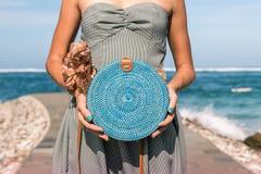 有外面时兴的时髦的蓝色藤条袋子和丝绸围巾的妇女手 巴厘岛,印度尼西亚热带海岛  藤条 免版税库存图片
