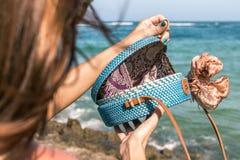 有外面时兴的时髦的蓝色藤条袋子和丝绸围巾的妇女手 巴厘岛,印度尼西亚热带海岛  藤条 库存图片