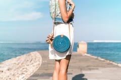 有外面时兴的时髦的蓝色藤条袋子和丝绸围巾的妇女 巴厘岛,印度尼西亚热带海岛  藤条 免版税图库摄影