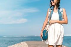 有外面时兴的时髦的蓝色藤条袋子和丝绸围巾的妇女 巴厘岛,印度尼西亚热带海岛  藤条 库存图片