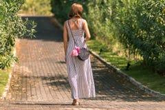 有外面时兴的时髦的藤条袋子和丝绸围巾的妇女 巴厘岛,印度尼西亚热带海岛  藤条提包和 库存照片