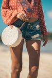 有外面时兴的时髦的藤条袋子和丝绸围巾的妇女 巴厘岛,印度尼西亚热带海岛  藤条提包和 免版税库存照片