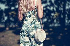有外面时兴的时髦的藤条袋子和丝绸围巾的妇女 巴厘岛,印度尼西亚热带海岛  藤条提包和 免版税图库摄影