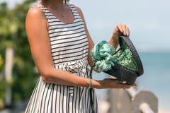 有外面时兴的时髦的藤条袋子黑色颜色和丝绸围巾的妇女 巴厘岛,印度尼西亚热带海岛  藤条 免版税库存照片